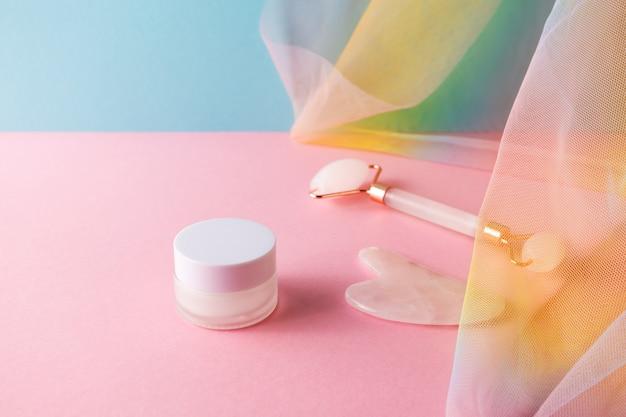 Vochtcrème, kwarts gezichtsroller en gua sha voor huidverzorgingsmassage op blauw roze achtergrond met kleurrijke regenboog organza draperie, close-up