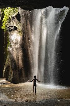 Vochtig klimaat. sportief meisje houdt haar arm wijd open terwijl ze geniet van het uitzicht op de waterval