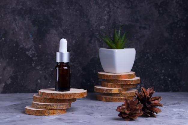 Vochtinbrengend serum met collageen en mucine van een slak voor de gezichtshuid tegen rimpels en acne in een glazen fles op houten steunen met groene vetplant op een grijze achtergrond