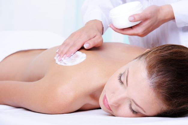 Vochtinbrengende crème op de vrouwelijke rug aanbrengen vóór de massage