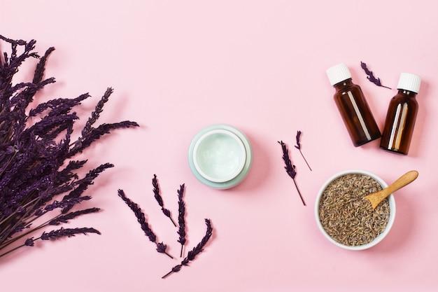 Vochtinbrengende crème op een roze achtergrond met lavendelbloemen in een bovenaanzicht