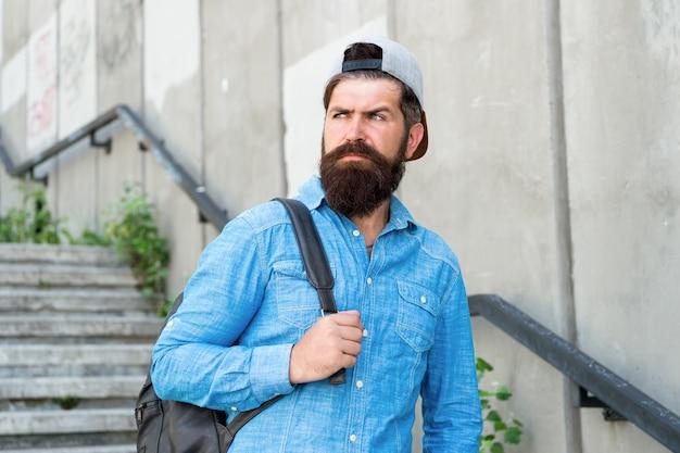 Voed je ziel met reizen. zelfverzekerde man lopen straat. mannelijke kapper zorg. brutale hipster met reisrugzak. wandelen avontuur concept. stedelijke stijl. rijpe hipster met baardreiziger. bebaarde man.