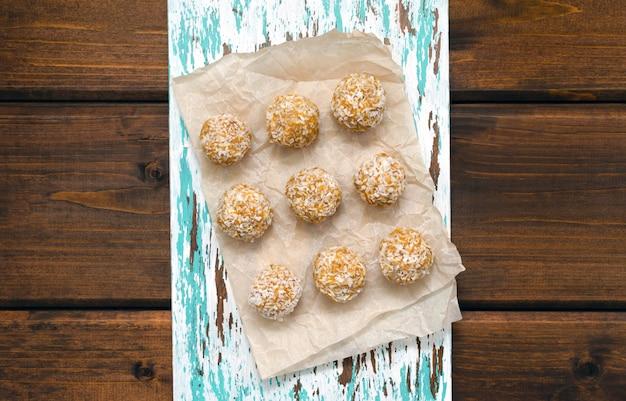 Voeding voor atleten gezonde snack. huisgemaakte gezonde energieballetjes gemaakt van natuurlijke ingrediënten van gedroogde havermout honing gedroogde vruchten noten in kokos suikervrij op een snijplank. uitzicht van boven