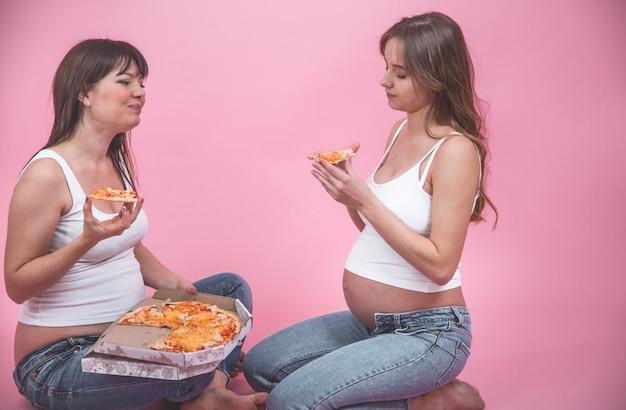 Voedingsconcept, zwangere vrouwen die pizza op een roze muur eten