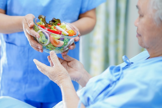 Voedingsdeskundige arts die en plantaardig ontbijt houden geven aan aziatische hogere vrouwenpatiënt in het ziekenhuis.