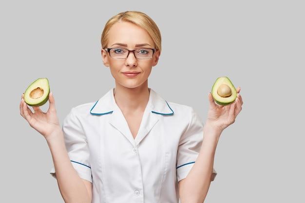 Voedingsdeskundige arts gezonde levensstijl concept - biologische avocado fruit te houden