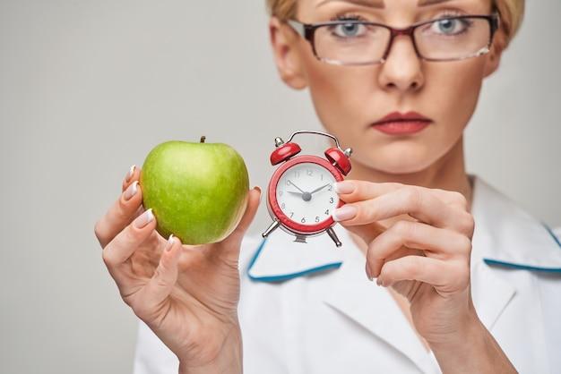 Voedingsdeskundige arts gezonde levensstijl concept - biologische verse groene appel en wekker te houden