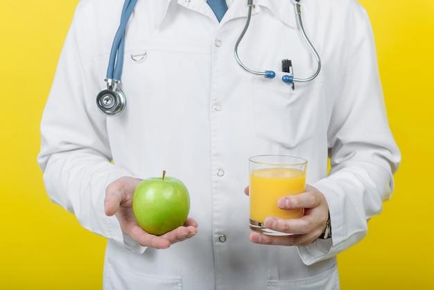 Voedingsdeskundige arts man met een glas sap en een appel