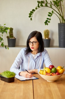 Voedingsdeskundige, diëtist die een dieetplan schrijft, met gezonde groenten en fruit, gezondheidszorg en dieetconcept. vrouwelijke voedingsdeskundige met fruit aan haar bureau.
