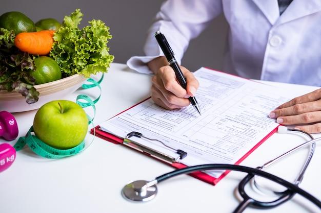 Voedingsdeskundige met gezond fruit, groente en meetlint, juiste voeding en dieet