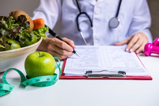 Voedingsdeskundige met gezond fruit, groente en meetlint werken, juiste voeding en dieet concept