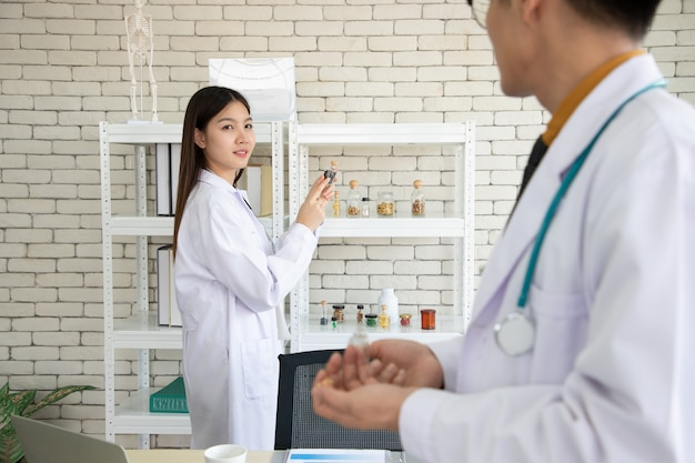 Voedingsdeskundige ontmoet en bespreekt met een jonge arts over de productie van essentiële vitamines en supplementen. ze onderzoeken en doen onderzoek in een laboratorium met een comfortabele werksfeer.