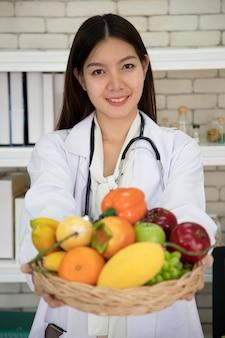 Voedingsdeskundigen die verschillende soorten fruit vasthouden, doen onderzoek en controleren de kwaliteit en eigenschappen. vitaminen en mineralen in fruit helpen het lichaam te versterken.
