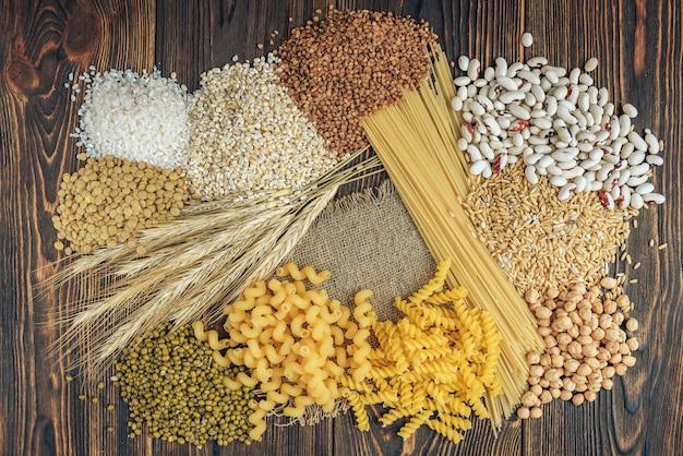 Voedingsmiddelen rijk aan koolhydraten op houten achtergrond. brood, pasta, parelgort en haver.