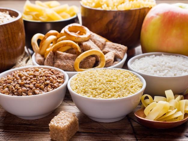 Voedingsmiddelen rijk aan koolhydraten op rustieke houten tafel.