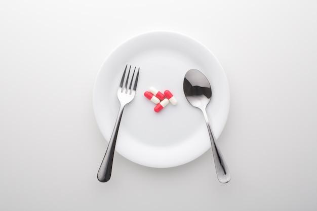 Voedingssupplement op witte plaat met lepel en vork, bovenaanzicht