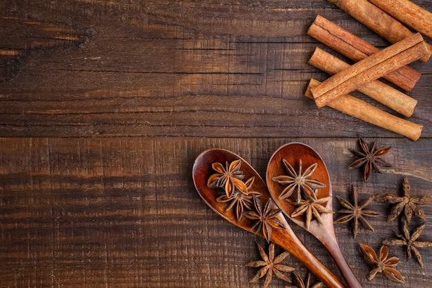 Voedsel achtergrond. anijs sterren in houten lepels. kaneelstokjes. zicht over.