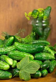 Voedsel achtergrond. biologische producten, gezonde voeding, oogsten voor toekomstig gebruik, groenten inmaken, komkommers inleggen. komkommers met knoflook, zout, dille en lege glazen pot voor beitsen.