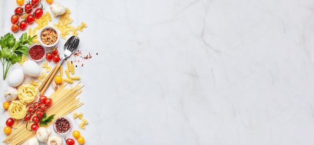 Voedsel achtergrond met plaats voor tekst, met verschillende soorten pasta, tomaten, kruiden, champignons, eieren, kruiderijen verspreid over lichte marmeren achtergrond, bovenaanzicht. italiaanse keuken concept