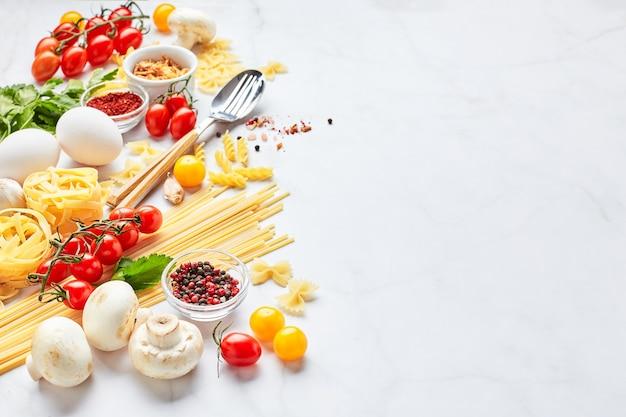 Voedsel achtergrond met plaats voor tekst, met verschillende soorten pasta, tomaten, kruiden, champignons, eieren, kruiderijen verspreid over lichte marmeren achtergrond. italiaanse keuken concept