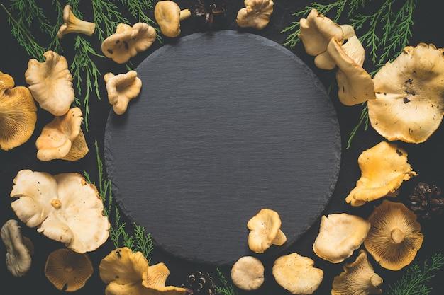 Voedsel achtergrond met wilde paddestoelen cantharellen rond een leisteen snijplank.