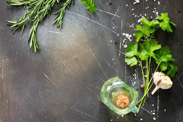 Voedsel achtergrond peterselie en rozemarijn op een donkere stenen tafel ruimte kopiëren