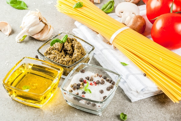 Voedsel achtergrondingrediënten voor het koken van diner. pasta groenten groenten sauzen en specerijen grijze stenen achtergrond