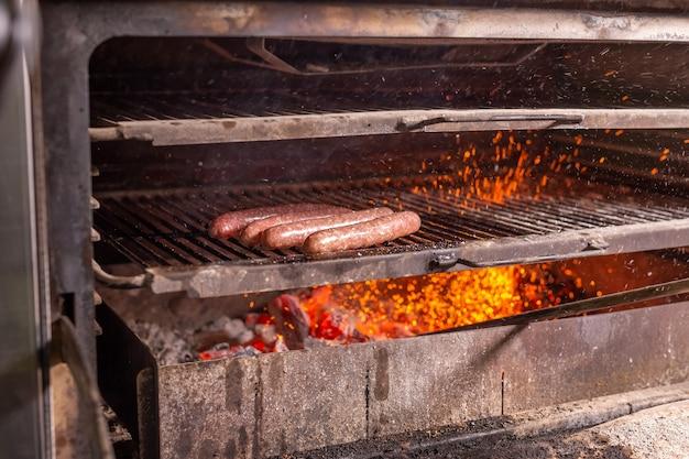 Voedsel, ambacht en heerlijk concept - worstjes koken op een grill.