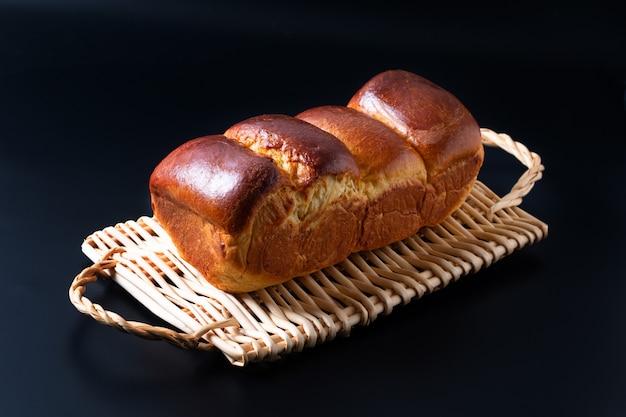 Voedsel bakken concept vers gebakken biologische zelfgemaakte zachte melk brood brood in brood pan op rieten brood lade