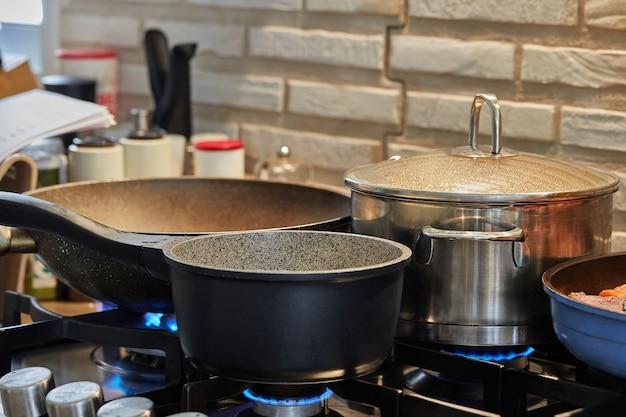Voedsel bereiden in koekenpan en stoofschotels op het gasfornuis in de keuken
