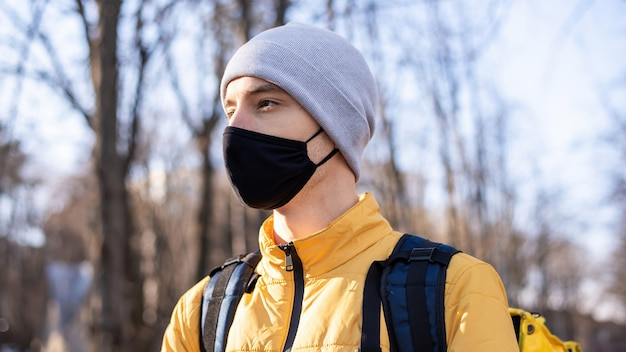Voedsel bezorger in een park. zwart medisch masker, gele rugzak en jas. winter