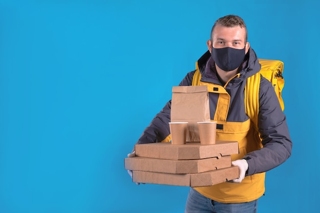 Voedsel bezorger met een medisch masker in een geel jasje