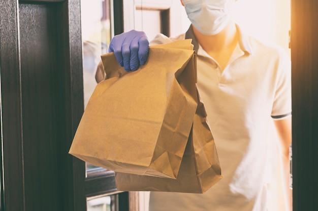 Voedsel bezorger met handschoenen en gezichtsmasker tijdens het geven van de bestelling
