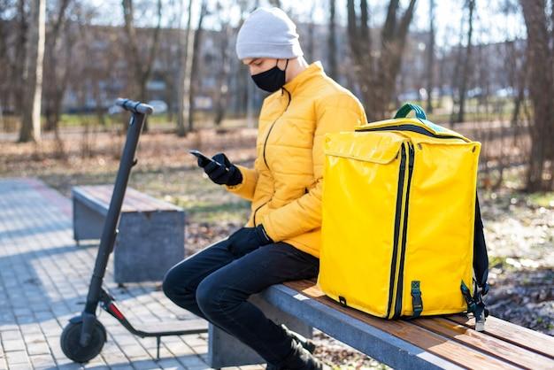 Voedsel bezorger met scooter in een park zittend op een bankje en met behulp van zijn smartphone. zwart medisch masker, gele rugzak en jas. winter