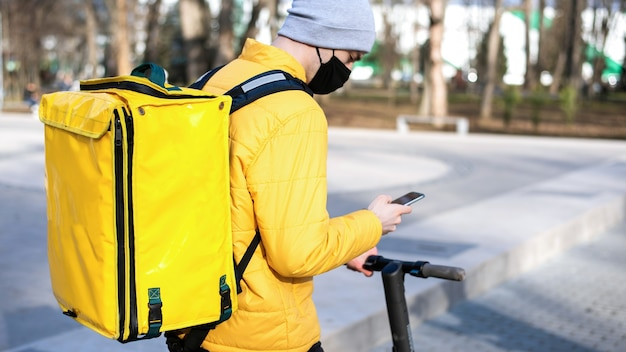 Voedsel bezorger op een scooter in een park met zijn smartphone. zwart medisch masker, gele rugzak en jas. winter