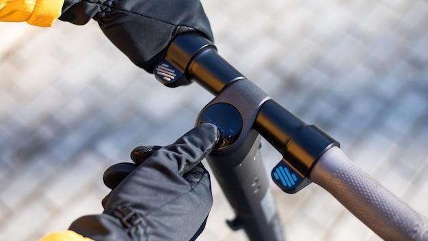 Voedsel bezorger op een scooter met zijn smartphone. geel jasje en zwarte handschoenen. winter