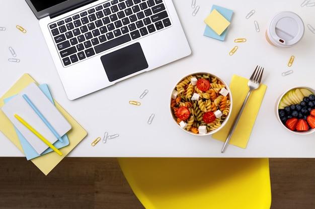 Voedsel bij het weghalen van dozen op witte lijst met laptop. online eten bezorgen.