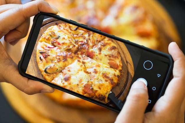 Voedsel blogger die foto van gekookte pizza neemt.