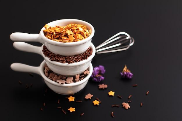 Voedsel concept decoratie suiker spinkles chocolade en gouden sterren in witte keramische kopjes