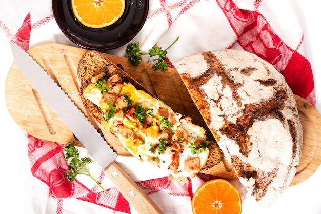 Voedsel concept organische franse sourdough geroosterd met eieren en ham op houten snijplank