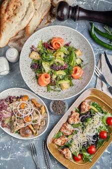 Voedsel concept, tafel met verschillende snacks geplaatst op. salade met zalm, caesar skuric, gepekelde champignons, brood.
