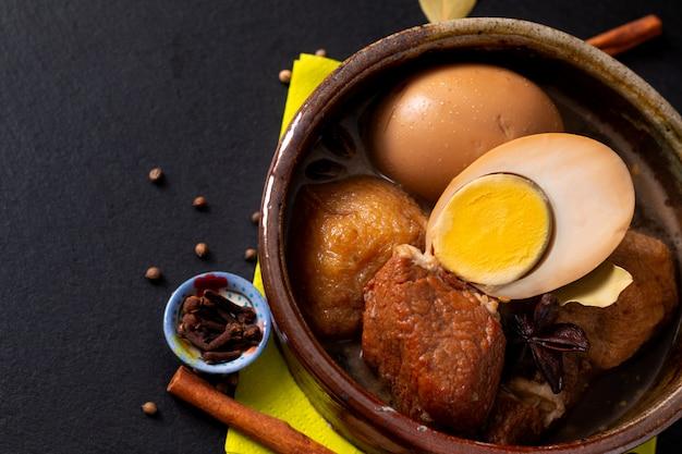 Voedsel concept thaise keuken varkensvlees buik en ei met vijf kruiden geurige stoofpot moo palo op zwarte leisteen