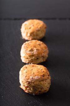 Voedsel concept vers gebakken zelfgemaakte boterachtige, zoute ham en kaas scones op zwart