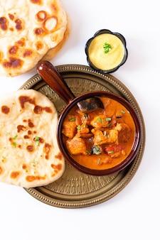 Voedsel concept zelfgemaakte tandoori chicken masala curry met naan brood en yoghurt onderdompelende saus