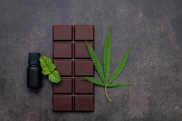 Voedsel conceptueel beeld van cannabisblad met donkere chocolade en vork op donker beton.