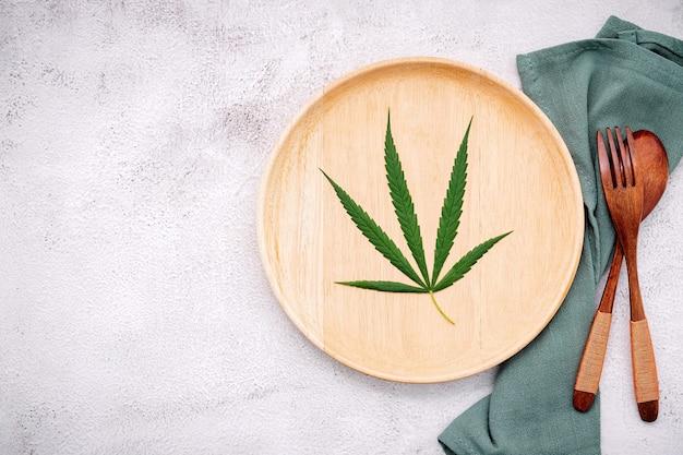 Voedsel conceptueel beeld van een cannabisblad met lepel en vork op wit beton.