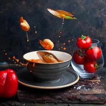 Voedsel dat in de lucht met tomaten op zwart geweven zijaanzicht vliegt als achtergrond