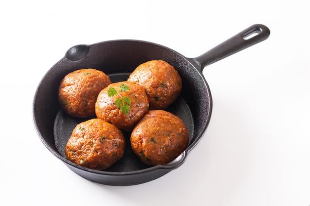 Voedsel eigengemaakt ruw organisch kruidig vleesballetje in ijzer dat op witte achtergrond wordt gegoten