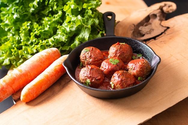 Voedsel eigengemaakte organische kruidige vleesballetje in ijzer dat op houten achtergrond wordt gegoten