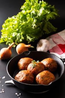 Voedsel eigengemaakte ruwe organische kruidige vleesballetje in ijzer dat op zwarte achtergrond wordt gegoten